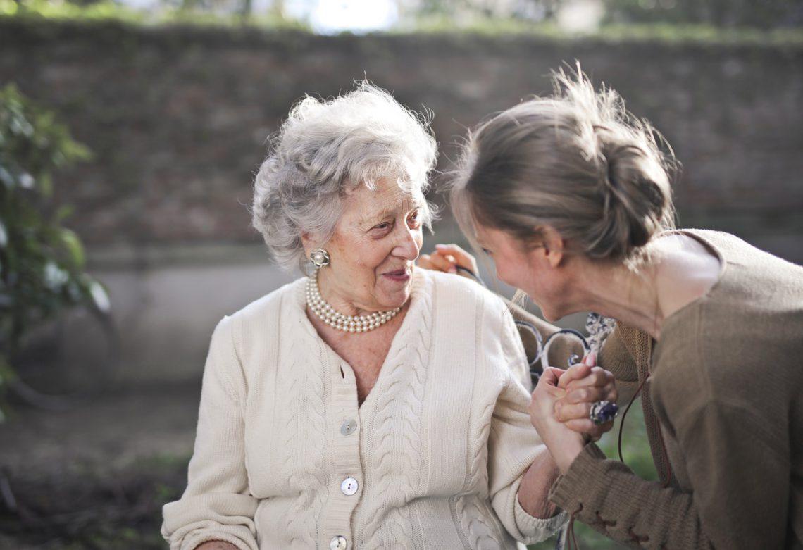 deux femmes âgées assises qui se tiennent la main